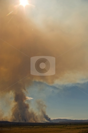 Smoke and Sun stock photo, A tall column of dark smoke from a wildfire obscures the sun. by Andrew Orlemann