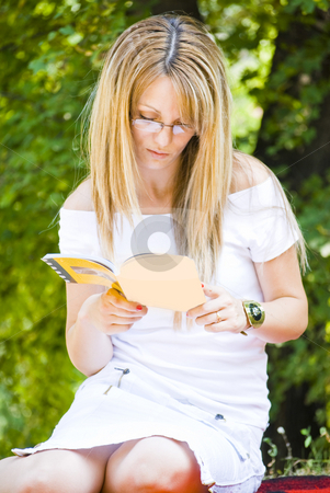 Beautiful young woman reading book stock photo, Beautiful young woman reading book outdoor by Desislava Dimitrova