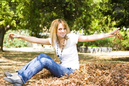 Beautiful young woman throwing leaves stock photo, Beautiful young model throwing leaves in park by Desislava Dimitrova