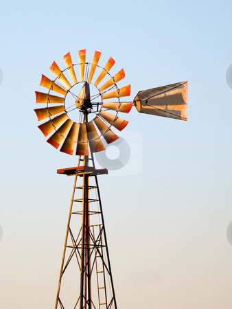 Antique Windmill Spins in the Setting Sun stock photo, Pumplng water from a well, an antique windmill spins slowly atop its tower on a farm in the midwestern United States. by Kenneth Keifer