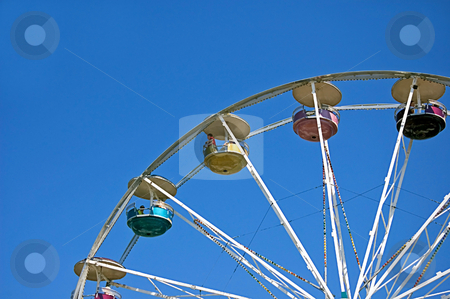 Carnival Ride Against Bright Blue Sky stock photo, This carnival ride is a large wheel with baskets against a bright blue sunny sky. by Valerie Garner