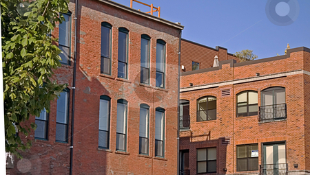 Old Style Brick City Buildings stock photo, Photo shows an old style brick buildings of a cityscape with bright blue sky and old town charm. by Valerie Garner