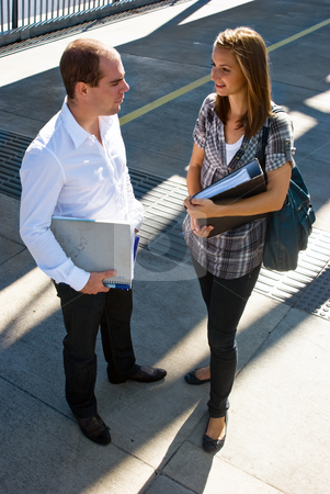 Two Students stock photo, Two students talking on a bridge, holding their notes by Corepics VOF
