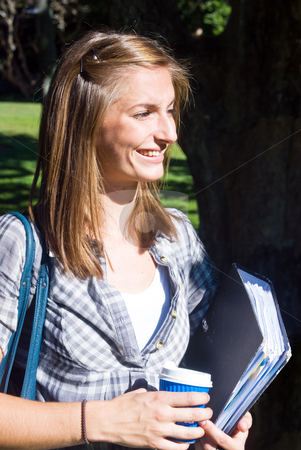Smiling student stock photo, Young female student, holding a dossier with notes and a cup of coffee, smiling in the sunlight by Corepics VOF