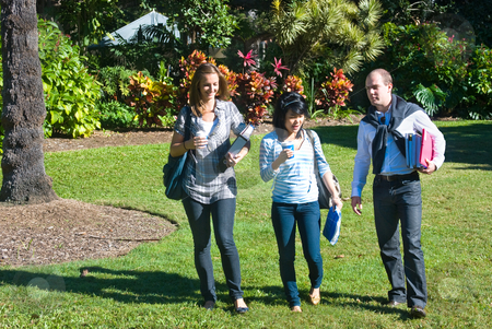 Students in the park stock photo, Three students walking through the botanical gardens, on their way to class by Corepics VOF