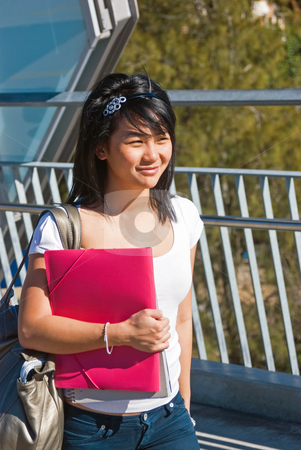 Smiling student stock photo, Young smiling Asian student holding a pink folder and wearing a tiara by Corepics VOF