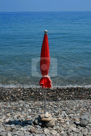 Beach umbrella stock photo, A folded red beach umbrella on an empty rocky beach beside an equally empty sea by Darren Booth