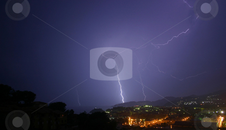 Lightning 1 of 3 stock photo, 3 lightning photos shot from the same viewpoint.  Same landscape, choice of bolts.  The image is taken from a high viewpoint, overlooking trees, a town and mountains.  This is my favourite of the 3 because of the almost 'batman'-like lighting and colour by Darren Booth