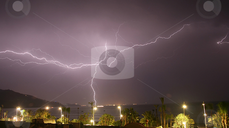 Lightning stock photo, A large multi-fork lightning burst grounding in a town across the bay.  The lights from fishing boats can be seen on the water.  Mountains in the background, palm trees and street lights in the foreground. by Darren Booth