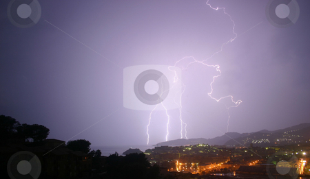 Lightning 2 of 3 stock photo, 3 lightning photos shot from the same viewpoint.  Same landscape, choice of bolts.  The image is taken from a high viewpoint, overlooking trees, a town and mountains. by Darren Booth