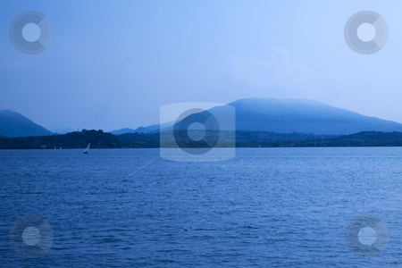 Blue lake stock photo, Blue landscape of lake with dark mountains and sails in the background by Fabio Alcini