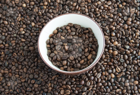 Coffee stock photo, A cup full of coffee beans, surrounded by other coffee beans by Fabio Alcini