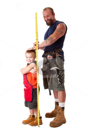 Dad measuring height of son stock photo, Father wearing tool belt with toy hammer and measuring tape, measures height of cute son dressed in orange apron, isolated. by Paul Hakimata
