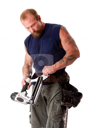 Man with nail gun stock photo, Strong man with tattoos loading a nail gun with nails, wearing a tool belt with hammer, isolated by Paul Hakimata