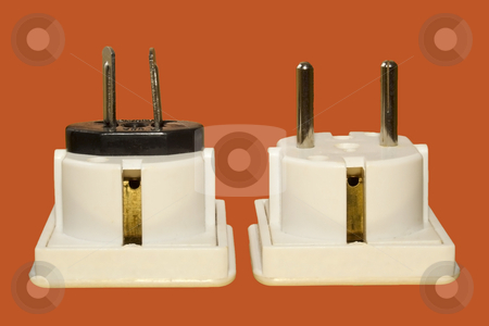 A pair of travel adaptors stock photo, A pair of travel adaptors on a bright orange background by Mike Smith