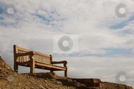 Cliff top seat stock photo, A traditional wooden bench on a cliff top view point under a summer sky by Mike Smith