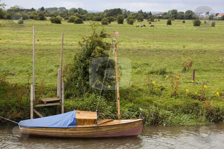 Small boat moored by canal stock photo, A small boat moored by a canal in summer by Mike Smith