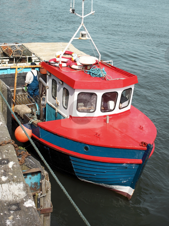 Fishing boat in a harbour stock photo, A fishing boat in a harbour in summer by Mike Smith