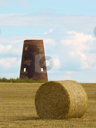 Old windmill stock photo, An old windmill in afield of round bales at harvest time in summer by Mike Smith