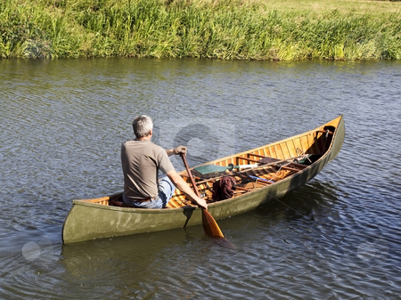 Man in a canoe stock photo, a man rowing a canoe down a small river on a beautiful summers day by Mike Smith