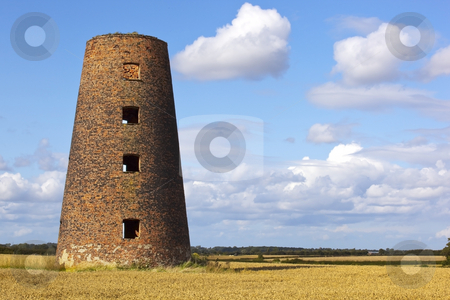 Old windmill 2 stock photo, An old weathered windmill in a field of wheat at harvest time in summer by Mike Smith