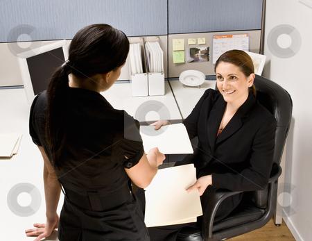 Businesswoman handing co-worker file folder stock photo, Businesswoman handing co-worker file folder by Jonathan Ross