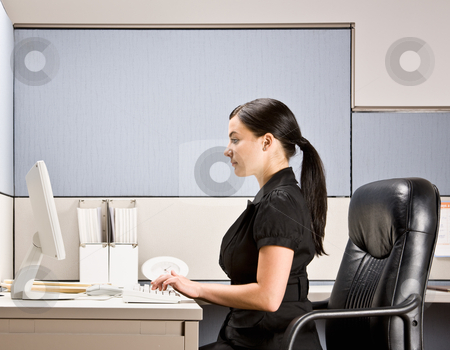 Businesswoman typing on computer at desk stock photo, Businesswoman typing on computer at desk by Jonathan Ross