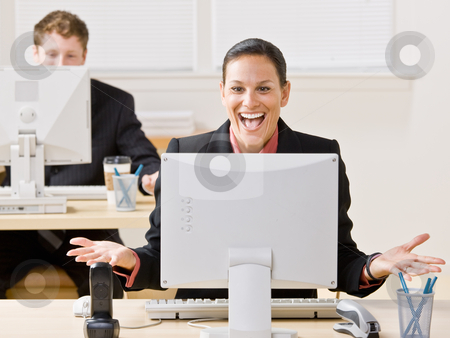 Businesswoman laughing at monitor stock photo, Businesswoman laughing at monitor by Jonathan Ross