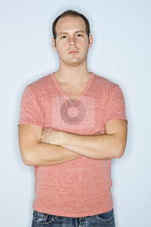 Man Standing with Arms Crossed stock photo, A man is standing against a wall with his arms crossed.  He is looking at the camera.  Vertically framed shot. by Jonathan Ross