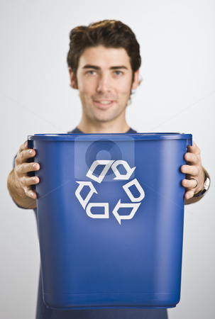 Man Holding Recycle Basket stock photo, A young man is holding a recycling basket and smiling at the camera.  Vertically framed shot. by Jonathan Ross