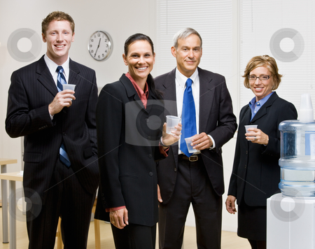Business people drinking water at water cooler stock photo, Business people drinking water at water cooler by Jonathan Ross