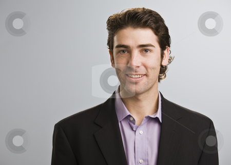 Man Smiling at Camera stock photo, A young businessman is standing in a room and smiling at the camera.  Horizontally framed shot. by Jonathan Ross