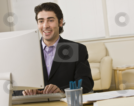 Businessman on Computer stock photo, A young businessman is working on a computer.  He is looking away from the camera.  Horizontally framed shot. by Jonathan Ross