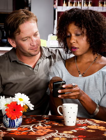 Mixed race couple in coffee house with cell phone stock photo, Caucasian man and African American woman in coffee house with cell phone by Scott Griessel