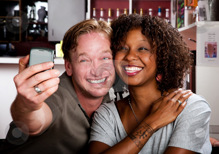 Mixed race couple in coffee house with taking picture cell phone stock photo, Caucasian man and African American woman taking picture in coffee house with cell phone by Scott Griessel