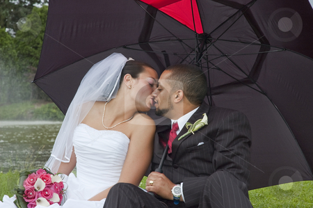 Married couple stock photo, Just married multi ethnic couple kissing under an umbrella by Vlad Podkhlebnik