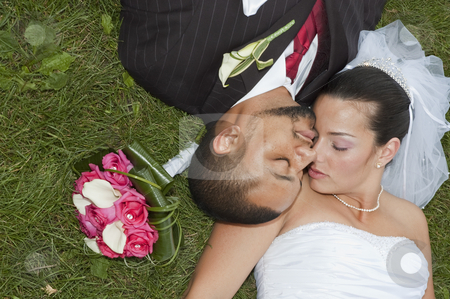 Married couple stock photo, Just married multi ethnic couple laying in the grass by Vlad Podkhlebnik