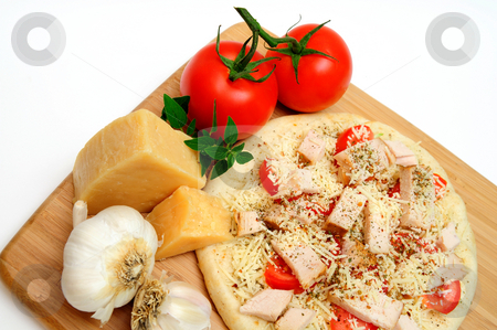Chicken Pizza stock photo, Ready to cook, Grilled chicken, fresh tomatoes, garlic and grated Asiago cheese top this gournet pizza for one topped off with dried herbs and spices with a block of parmesan cheese on the side by Lynn Bendickson