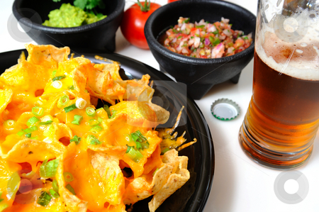 Nachos and Beer stock photo, Cheese nachos with sides of guacamole and salsa with an ice cold bottled beer poured in a glass by Lynn Bendickson