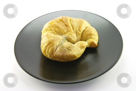 Croissant on a Black Plate stock photo, Single golden flakey delicious baked croissant on a black plate with a white background by Keith Wilson
