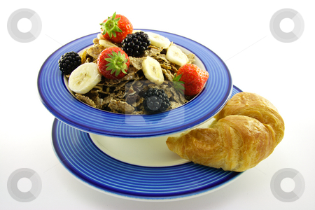 Bran Flakes in a Blue Bowl stock photo, Crunchy looking delicious bran flakes and juicy fruit in a blue bowl with a croissant on a white background by Keith Wilson