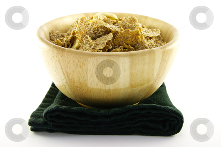 Bran Flakes in a Woodden Bowl stock photo, Crunchy delicious looking bran flakes in a wooden bowl and a black napkin on a white background by Keith Wilson