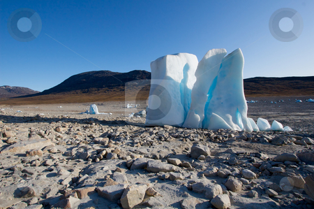 Iceberg in the middle of a dried out lake stock photo, Dried out lake, right by a glacier. There are melting icebergs all around. The one in the front is actually about 20 meters/65 feet high all though you can't tell from the photo. by Anders Peter