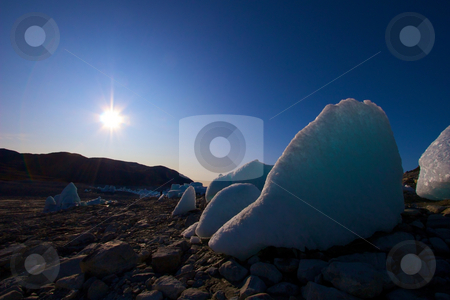 Ice in the middle of a dried out lake stock photo, Dried out lake, right by a glacier. There are melting icebergs all around some as high as 20 meters/65 feet. by Anders Peter
