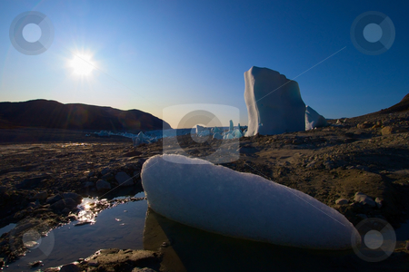 Ice in a dried out lake - glacier in the background stock photo, Dried out lake, right by a glacier. There are melting icebergs all around some as high as 20 meters/65 feet. The glacier is seen in the background. by Anders Peter