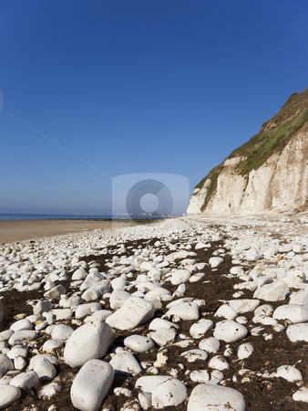 View of a seaside town stock photo, View across the bay to bridlington from danes dyke with white limestone cliffs and rocks under a bright blue summer sky by Mike Smith