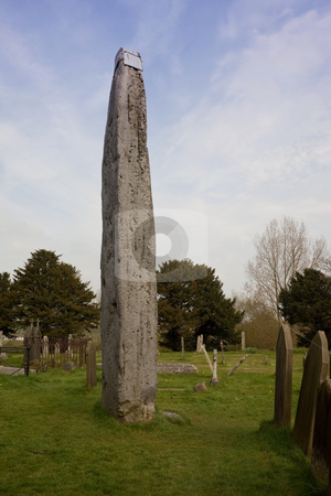 Standing stone in churchyard stock photo, A standing stone in a churchyard in spring by Mike Smith
