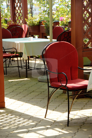 Red chair in patio of outdoor cafe  stock photo, Summer patio cafe restaurant chairs and tables by Julija Sapic