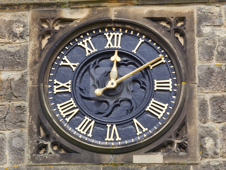 Ornamental clock stock photo, Ornamental gilded clock mounted on stone wall by Mike Smith