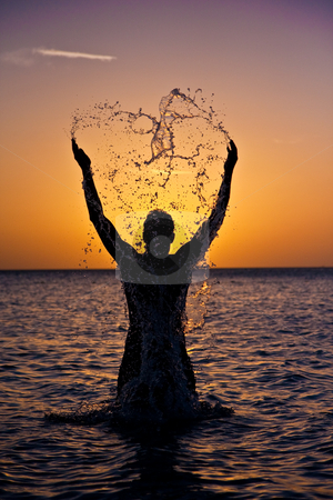 Heart-Shaped Splash stock photo, Man splashes in the water, silhoutted at sunset. by Tyson Koska